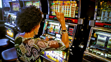 woman celebrating after winning at a casino slot machine